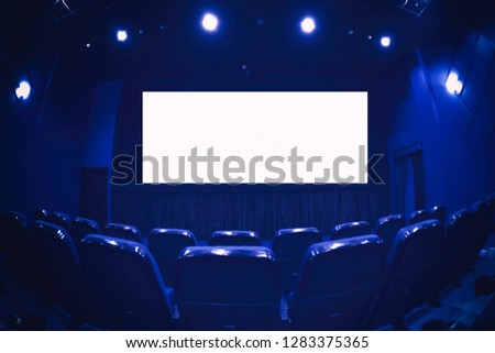 Empty cinema auditorium with empty white screen. Empty rows of theater or movie seats. Blue toned. #1283375365