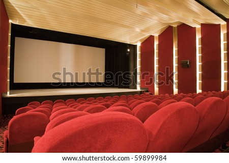 Empty cinema auditorium with line of chairs and projection screen. Ready for adding your own picture. Side view.