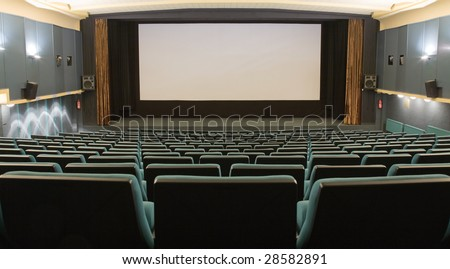 Empty cinema auditorium with line of green chairs and silver screen. Ready for adding your own picture.