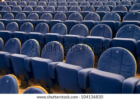 Empty cinema auditorium with lines of blue chairs.