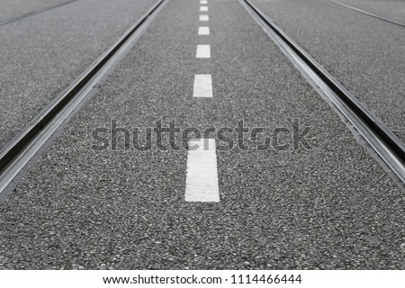 Empty city street with white dotted line and parallel tram tracks