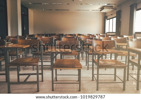 Empty classroom with a lot of chair with no student. Empty classroom with vintage tone wooden chairs. Back to school concept.