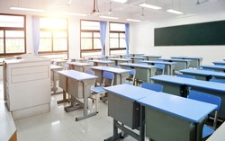Empty classroom with blue desks and chairs.