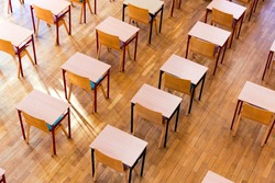 Empty classroom with wooden benches and chairs.