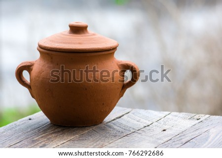 Empty clay pot on a wooden table in garden