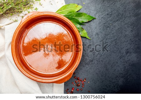 Empty clay pot with pepper, bay leaf and thyme. On black background. Concept to include your food and your text.