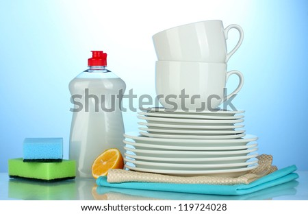 empty clean plates and cups with dishwashing liquid, sponges and lemon on blue background