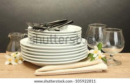 empty clean plates and glasses on wooden table on grey background - stock photo