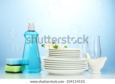 empty clean plates and glasses with dishwashing liquid, sponges and flowers on blue background