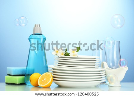empty clean plates and glasses with dishwashing liquid, sponges and lemon on blue background