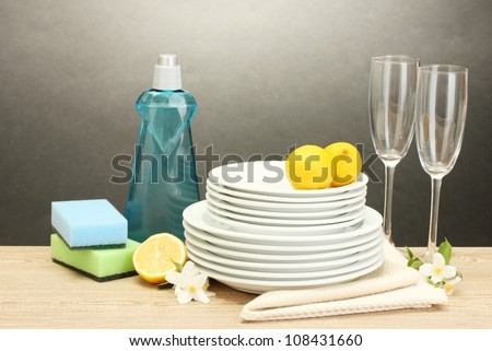 empty clean plates and glasses with dishwashing liquid, sponges and lemon on wooden table on grey background