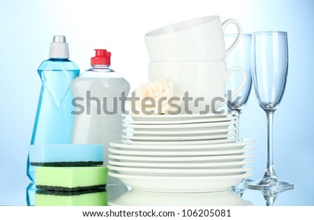 empty clean plates, glasses and cups with dishwashing liquid and sponges on blue background