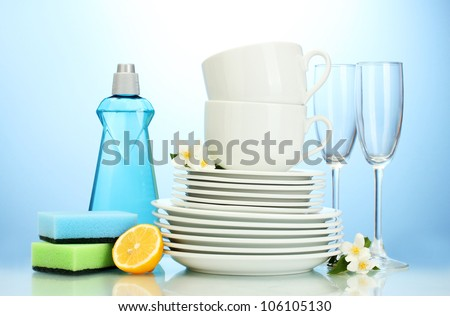 empty clean plates, glasses and cups with dishwashing liquid, sponges and lemon on blue background