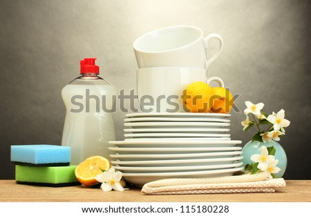 empty clean plates, glasses and cups with dishwashing liquid, sponges and lemon on wooden table on grey background