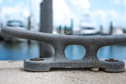 Empty coastal mooring or towing bollard for the boat, yacht or vessel. Bkue sky and marina as a background.