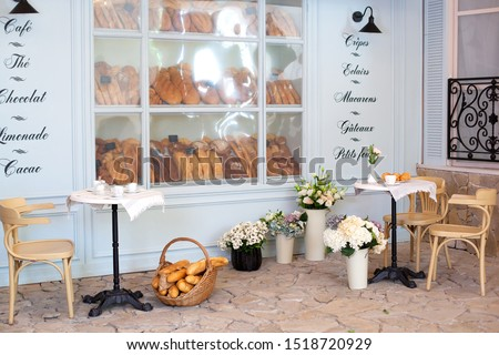 Empty coffee and restaurant terrace with tables and chairs in the French style. Freshly baked pastries, buns and bread in a bakery display case. Street cafe decoration, interior concept. Decor bakery. #1518720929