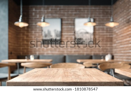 Empty coffee table over defocused coffee shop background with copy space