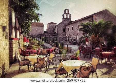 Empty coffee terrace with tables and chairs in old town of Budva on sunny day at sunset, Montenegro. Filtered image, vintage effect applied. Grunge