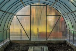 Empty color greenhouse before spring time with concrete walls and plastic construction