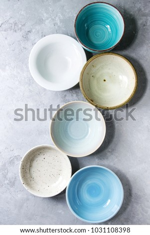 Empty colorful ceramic bowls collection. Various of dishware grey texture background. Top view #1031108398
