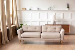 Empty comfy couch, contemporary furniture inside of cozy light sunny living room interior. Wooden clean floor with underfloor heat. Real estate, loan or rent, renovation remodelling service ad concept