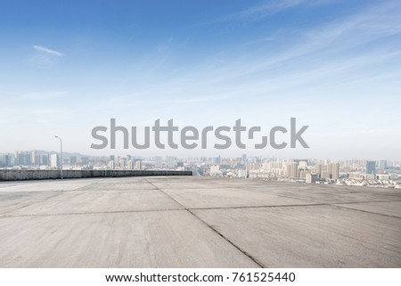 empty concrete floor and cityscape of shaoxing in blue foggy sky