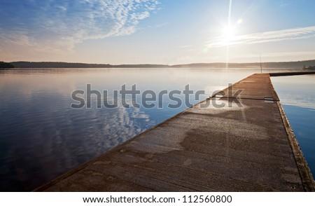 Empty concrete pier in the light of raising sun