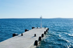Empty concrete pier with white signal lighthouse in the port of Croatian island Silba, beautiful blue Adriatic sea