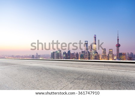 empty concrete road and cityscape in blue sky at dawn
