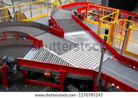 Empty conveyor sorting belt at distribution warehouse. Distribution hub for sorting packages and parcels delivered by air transportation. #1270785247