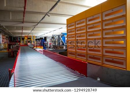 Empty conveyor sorting belt at distribution warehouse. Distribution hub for sorting packages and parcels delivered by air transportation. #1294928749