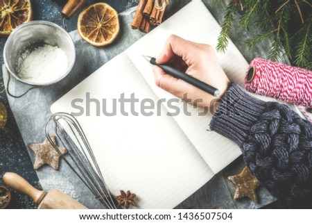 Empty cookbook for Christmas recipes, on dark blue concrete background with ingredients for traditional xmas baking, top view copy space
