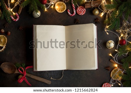 Empty Cookbook for Christmas recipes on dark table. Cook book with festive Christmas decor and spices.