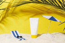 empty cosmetic skin care cream or sun block on sand beach with yellow background travel vacation accessory