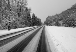 """Empty country road at an upgrade slope near the """"Nordhelle"""" peak in Sauerland Germany after heavy snowfall at the onset of winter in January. Danger of slithering on black ice or frozen snow tracks."""