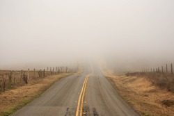 Empty country road disappears into thick fog