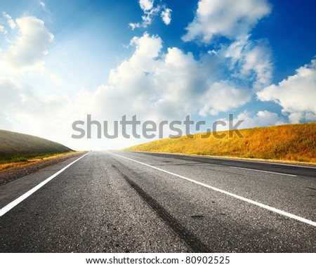 Empty countryside asphalt road and blue sky with clouds