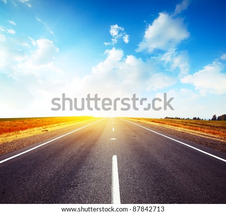 Empty countryside asphalt road and cloudy blue sky