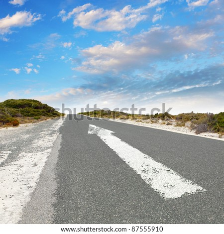 Empty countryside road with white arrow sing on it