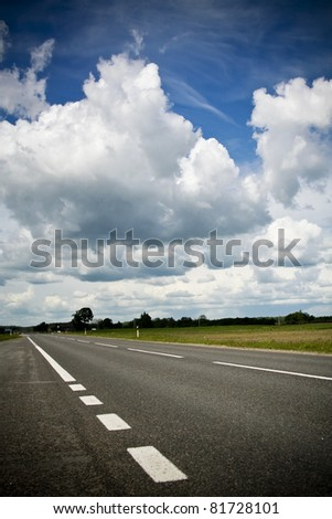 Empty countryside's road with the beautiful clouds and sky above