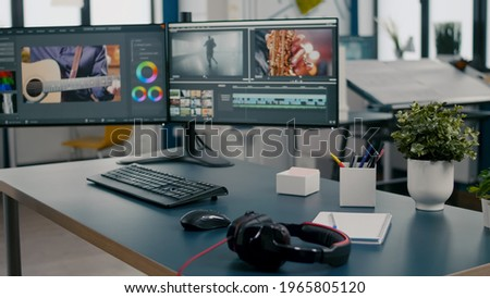 Empty creative multimedia studio with professional computer placed on desk, dual monitor setup. Video editing start up company agency with no people in it and post production software on pc displays Stock fotó ©