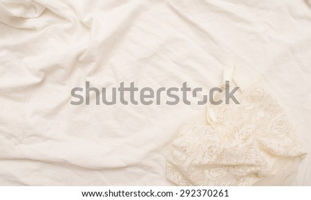 Empty crumpled white bed sheet and white silk lingerie.