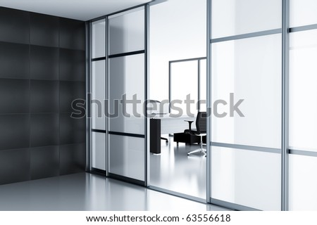 Empty cubicle with laptop on table behind a glass doors in modern office