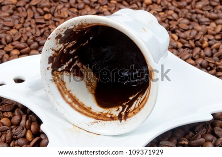Empty cup of black coffee with coffee sediment, traditionally using for fortune telling, with copy-space on the coffee beans - stock photo