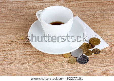 Empty cup of coffee with coins tip on wooden background. Ukrainian coins
