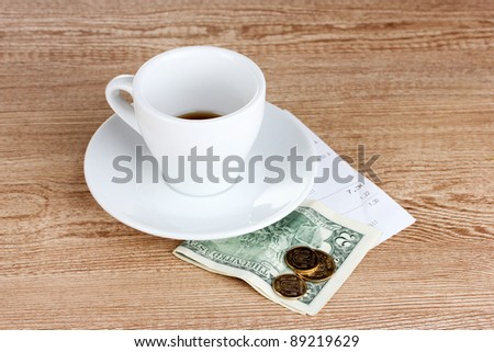 Empty cup of coffee with five dollars tip on wooden background