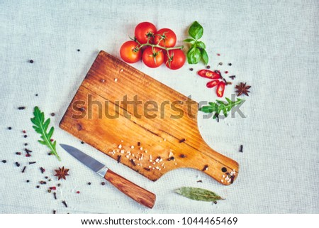 Empty cutting board and fresh tomato, spices, basil, arugula and knife on rustic background, top view