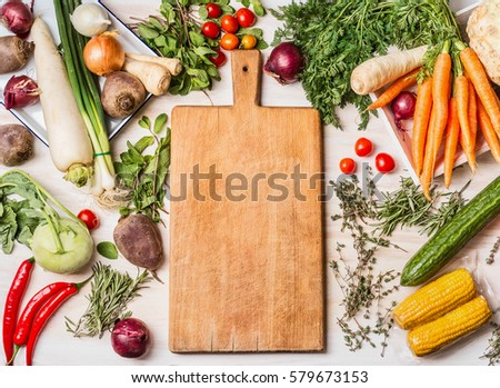 Empty cutting board and various raw vegetables for  tasty and healthy  cooking, top view, place for text, frame. Vegan or vegetarian food concept #579673153