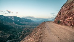 Empty dangerous narrow cliffside  mountain road. Dangerous off road driving along mountain edge and steep cliff. Dagestan.