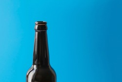 Empty dark bottle without cork and label on a blue background